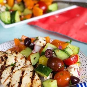 Greek Salad on a white plate with grilled chicken.