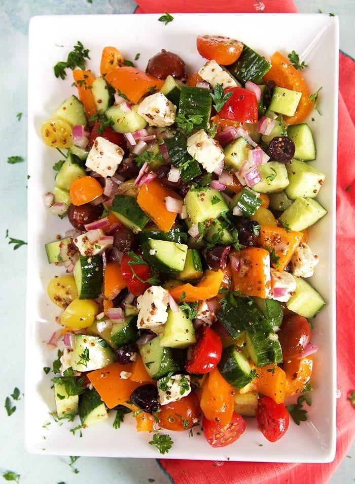 Overhead shot of Greek salad on a white platter.