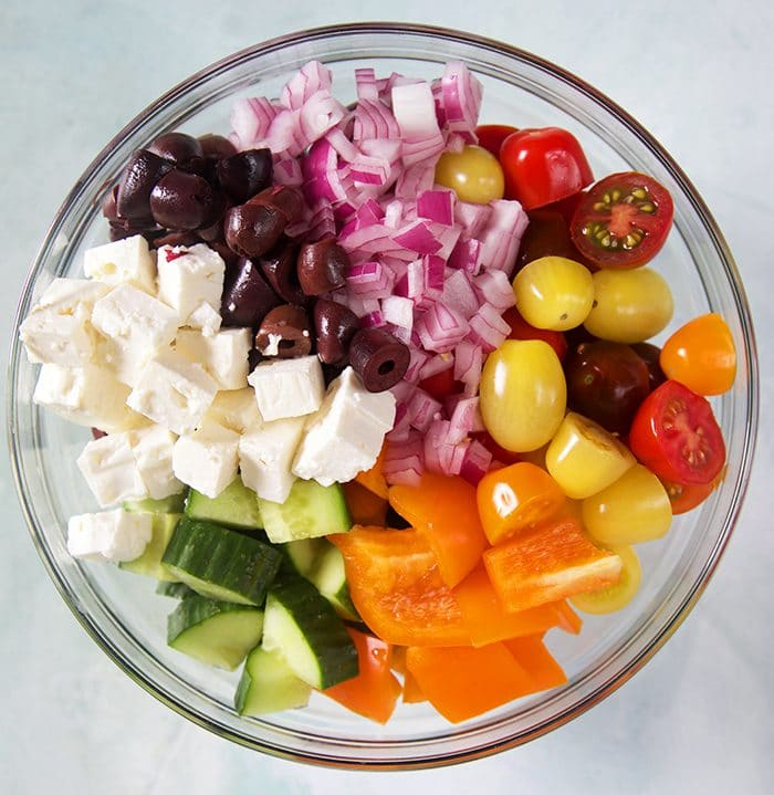 ingredients for greek salad in a glass bowl.