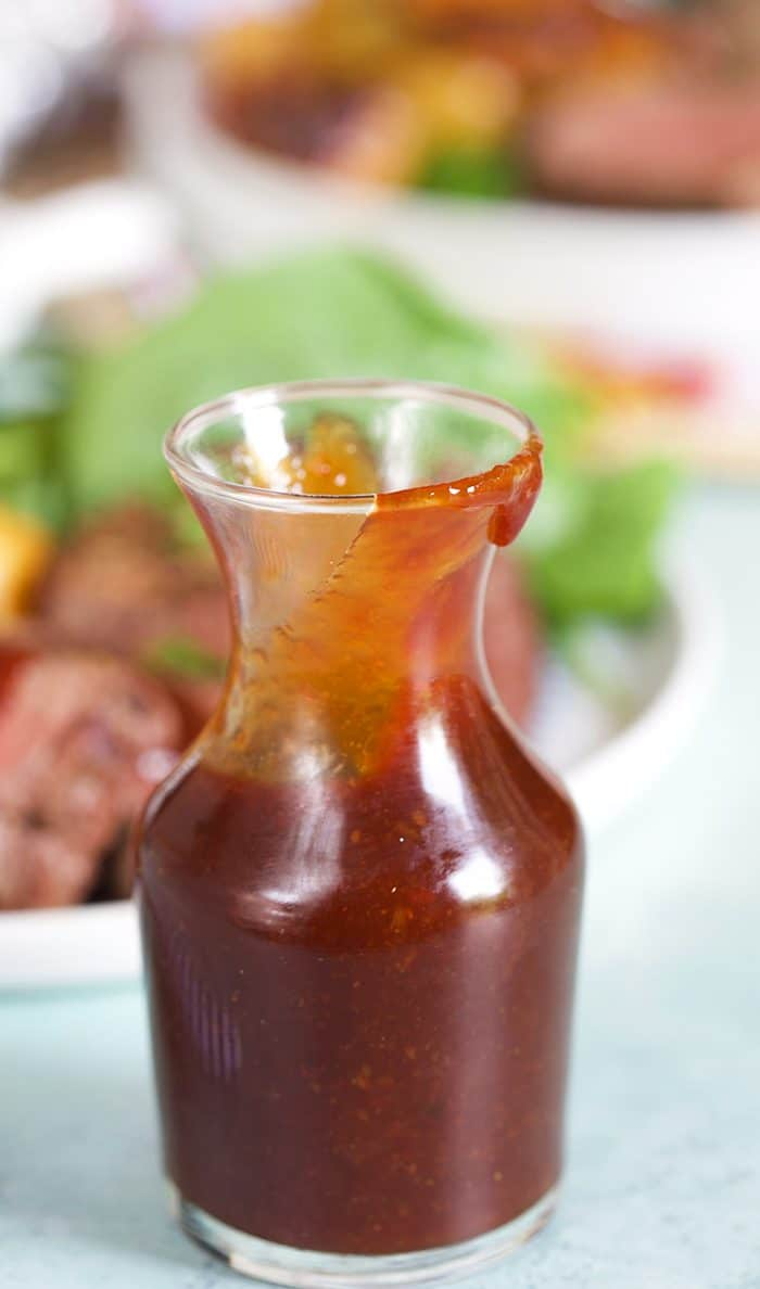 Steak sauce in a small bottle on a blue background.