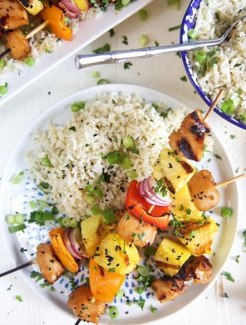 Overhead shot of teriyaki chicken skewers on a bed of white rice.