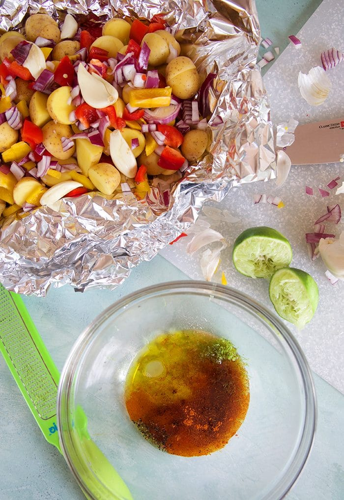 Fajita dressing being made to be poured over potatoes in a foil packet.