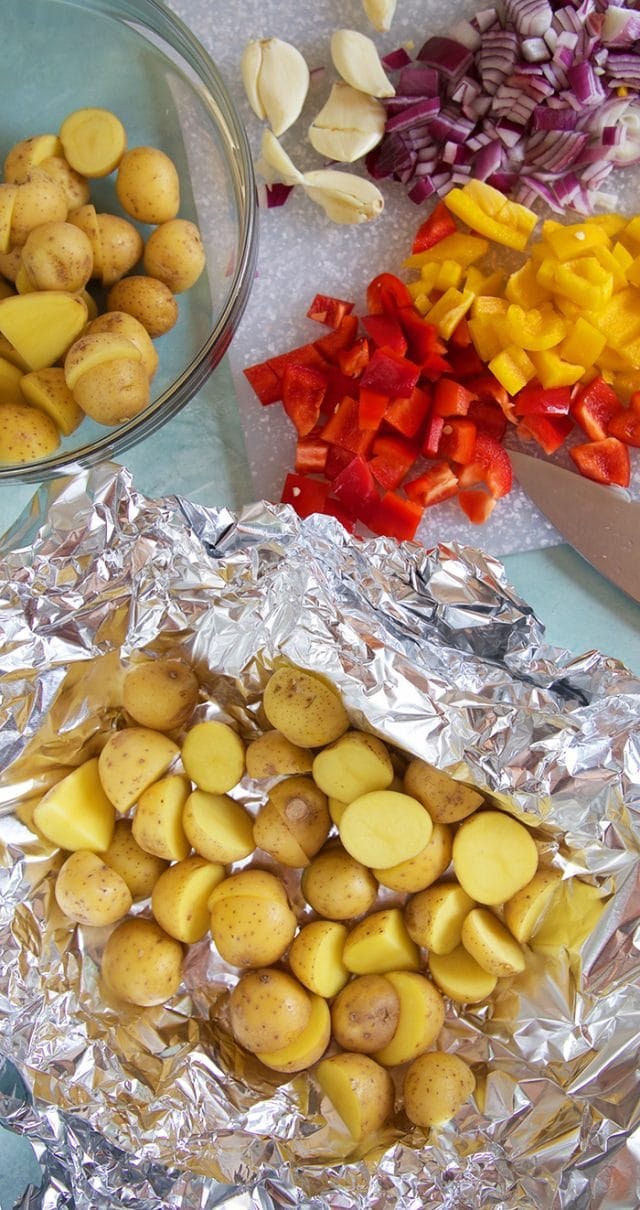 Potatoes in a foil packet with peppers and onions on the side getting ready to be tossed together.