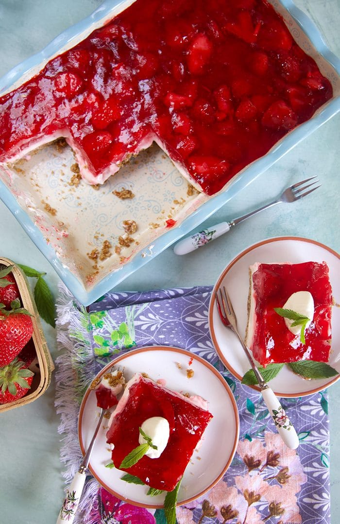 overhead shot of two slices of strawberry pretzel salad and a baking dish.