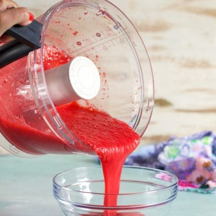 Strawberry puree being poured into a bowl.