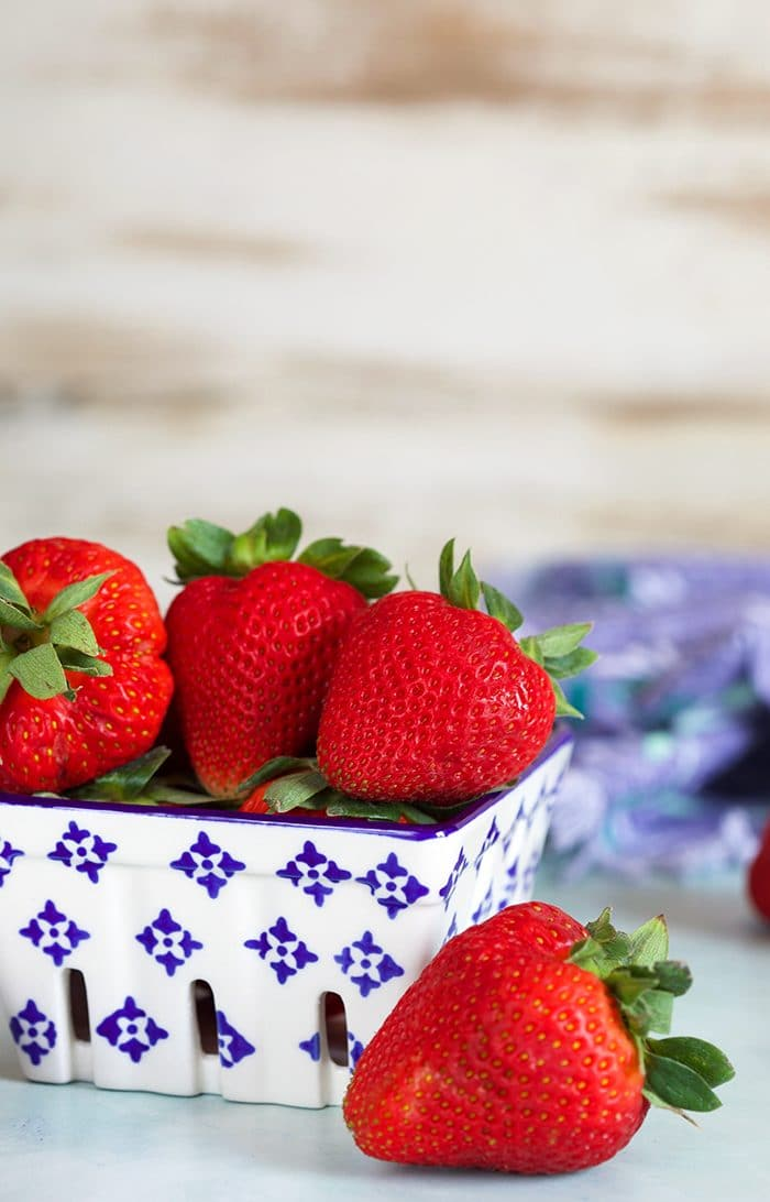 Strawberries in a ceramic blue and white berry container.