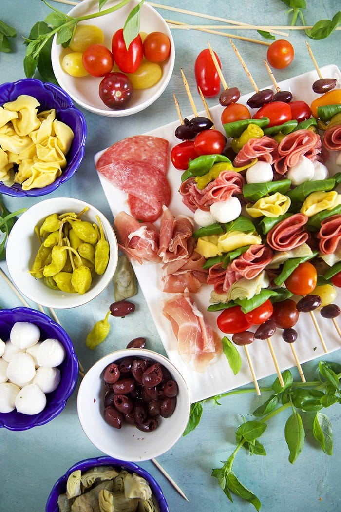 Antipasto skewers on a white platter being assembles with ingredients in the blue bowls.