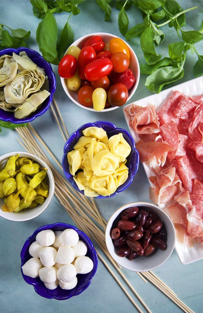 Ingredients for antipasto skewers in blue bowls and charcuterie on a platter.