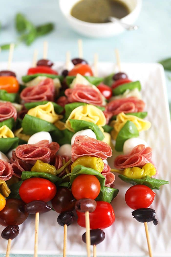 Antipasto Skewers on a white platter with pesto in a white bowl.