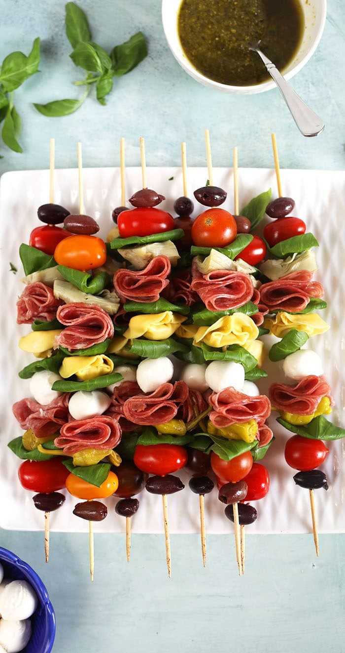 Overhead shot of Antipasto skewers on a white square plate with a bowl of pesto in the upper right corner.