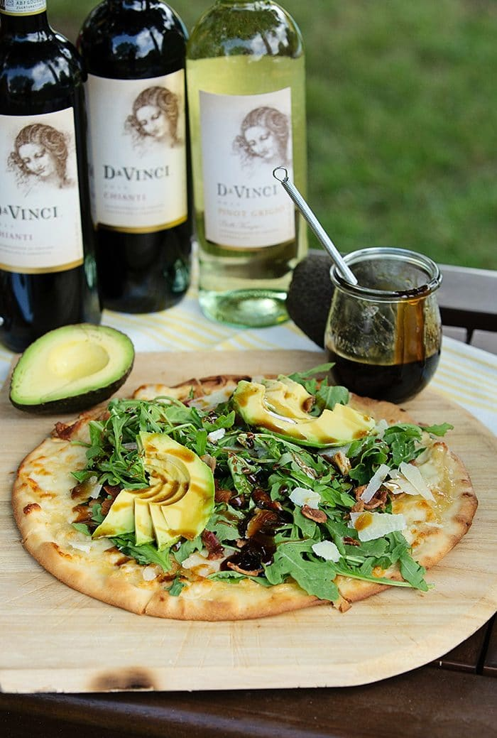 pizza on a wooden pizza peel with arugula and avocado.