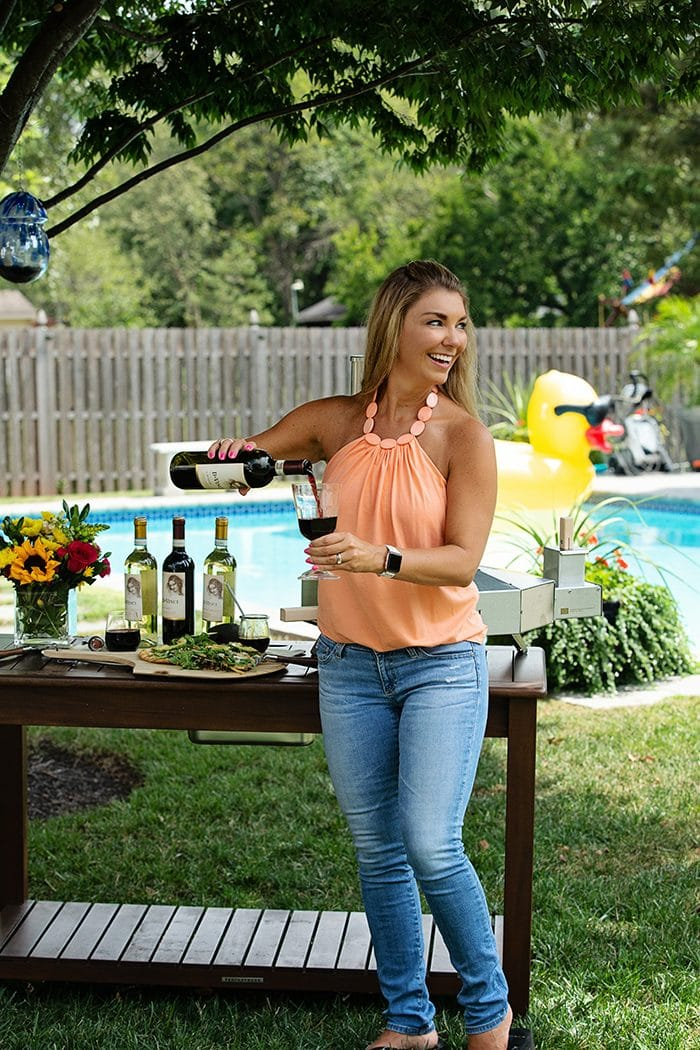 Kellie from the Suburban Soapbox pouring a glass of DaVinci Chianti Wine by a pool.