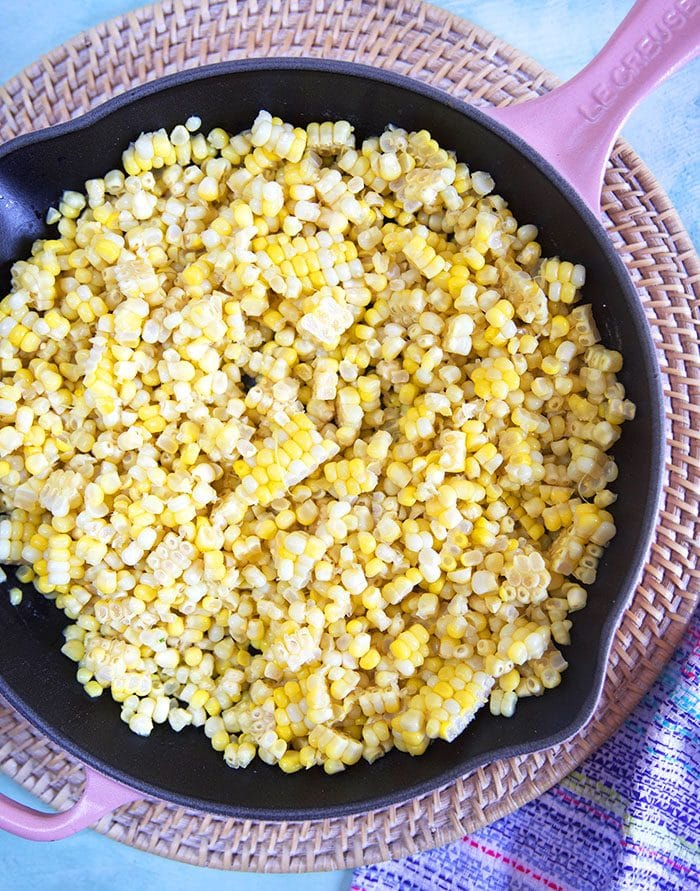 Sweet corn in a pink cast iron skillet