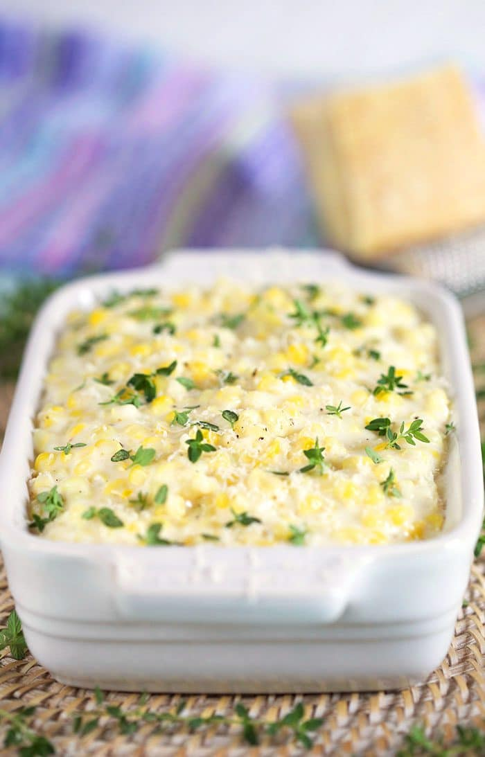Creamed Corn in a white dish with a wedge of cheese in the back.