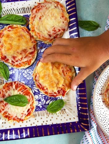 Child's hand taking an english muffin pizza off a blue and white platter.
