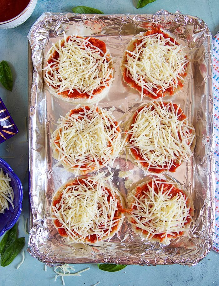 English Muffin Pizzas on a baking sheet with foil prior to baking.