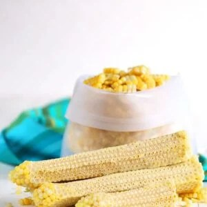 Corn off the cob in a freezer bag with cobs stacked in front.