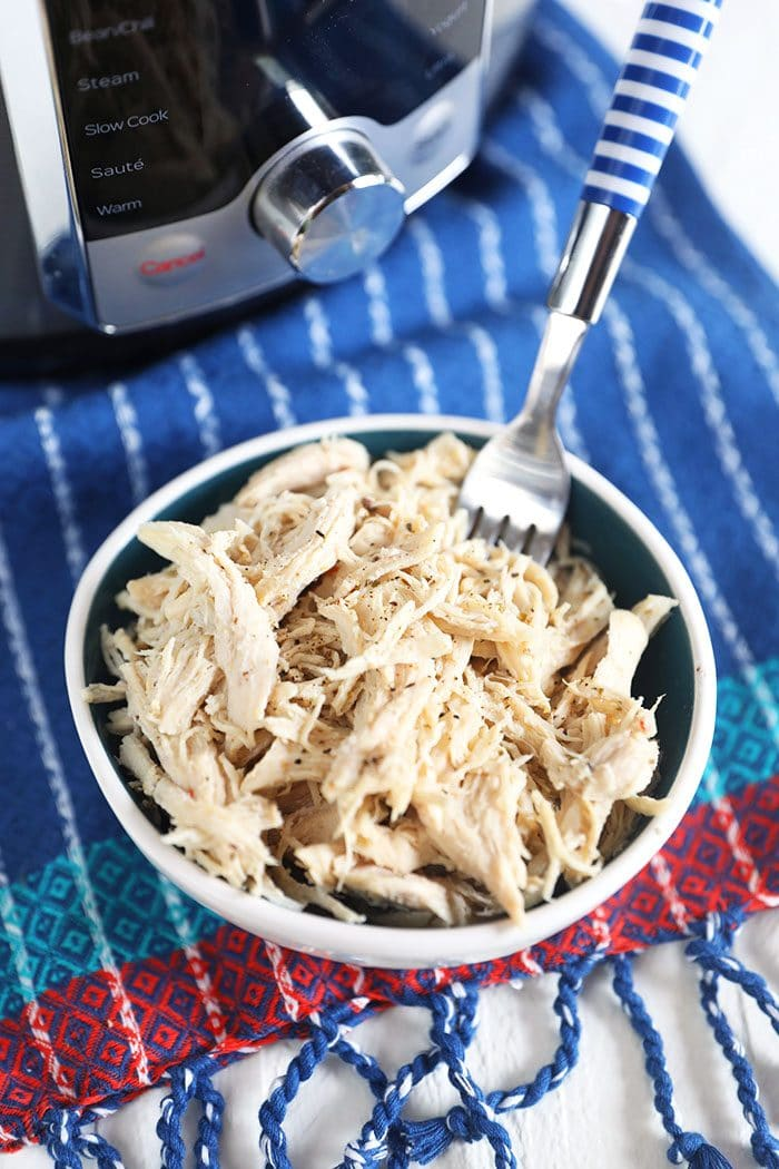 Shredded chicken breast in a white bowl with a fork on a blue and white striped napkin.