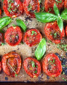 Close up of oven roasted tomatoes with basil and herbs.