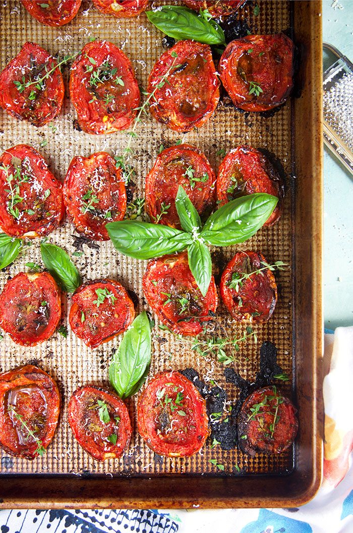 Overhead shot of roasted tomatoes on a baking sheet with basil and herbs.