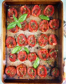 Oven roasted tomatoes on a baking sheet with basil and herbs.