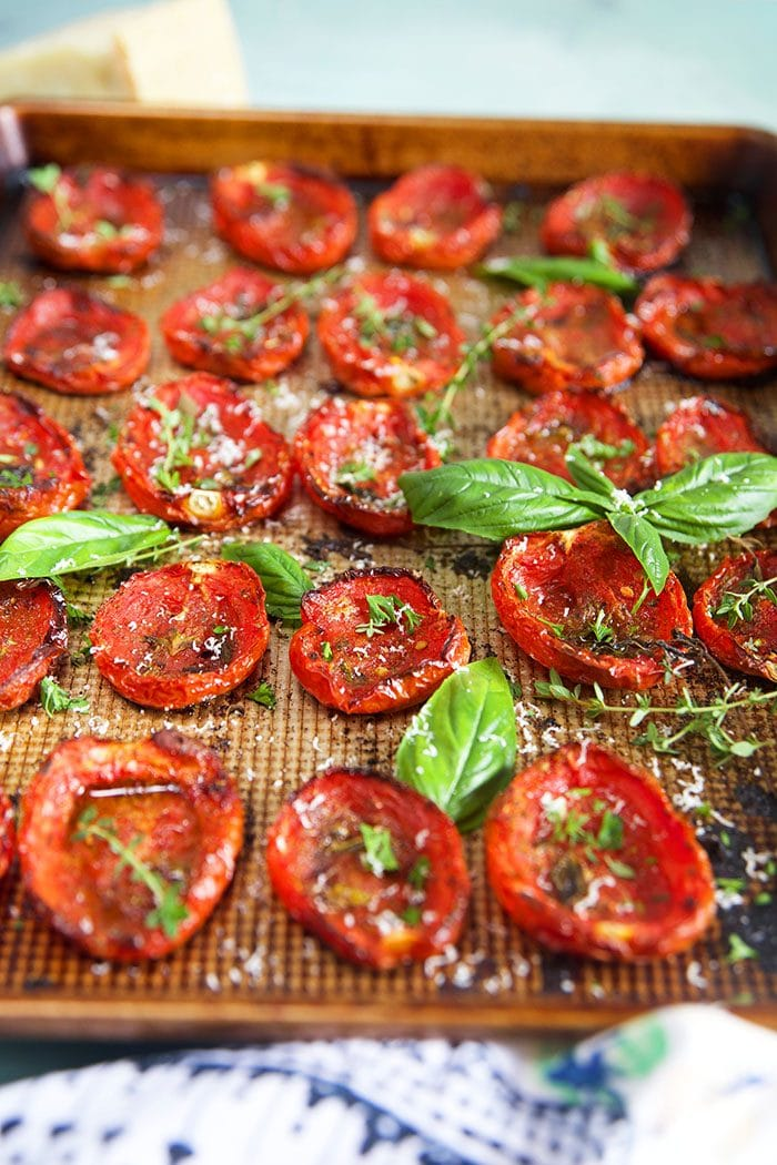 Side shot of oven roasted tomatoes on a baking sheet