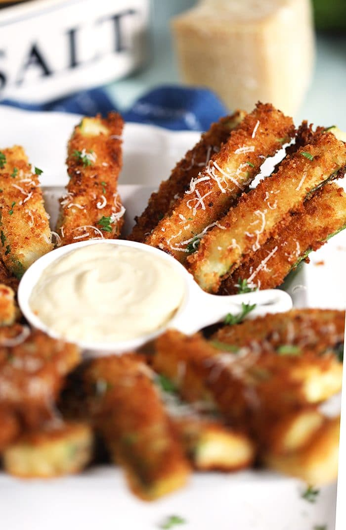 Close up of zucchini fries on a white platter.