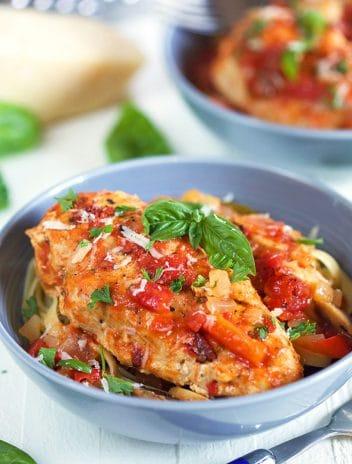 Chicken cacciatore in a blue bowl over pasta.