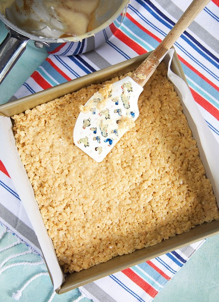 Peanut Butter Rice Krispies being pressed into a baking pan.