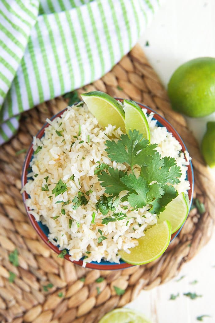 Overhead shot of cilantro lime rice with lime wedges and cilantro on a wicker place mat.