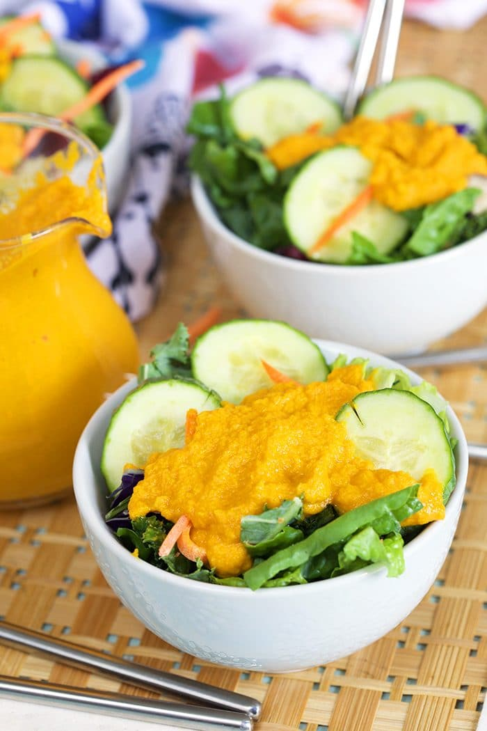 Green salad in a white bowl with carrot ginger dressing.