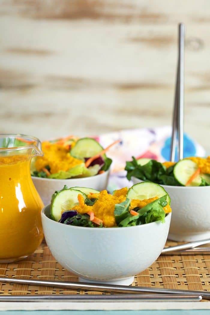 Green salad in white bowls with ginger dressing in a glass pitcher.