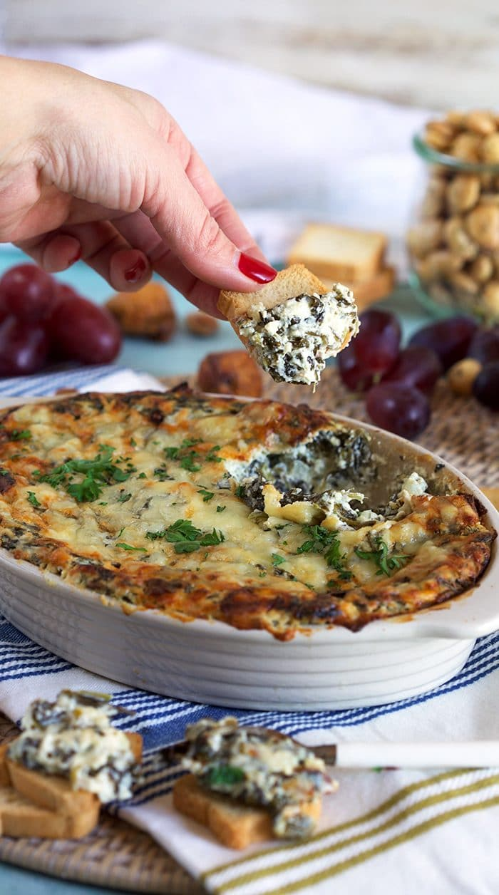 Hot Spinach Dip with a chip dipped into it.
