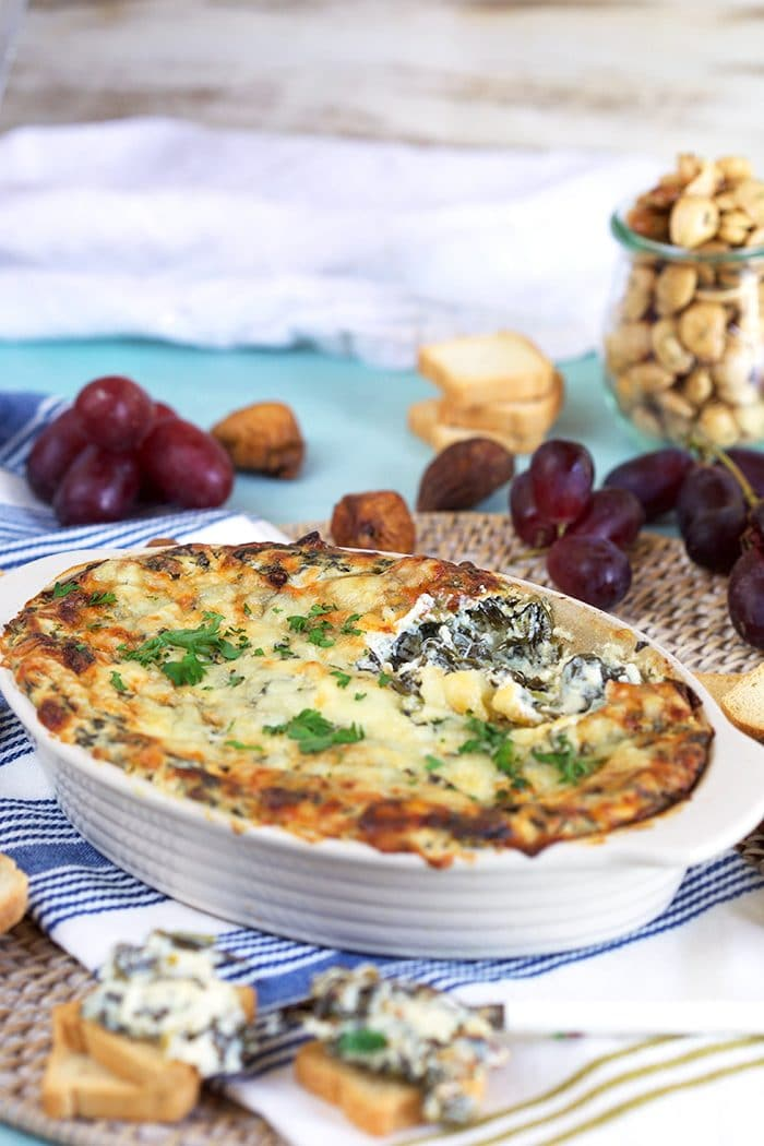 Hot spinach dip in a white casserole dish on a blue background.