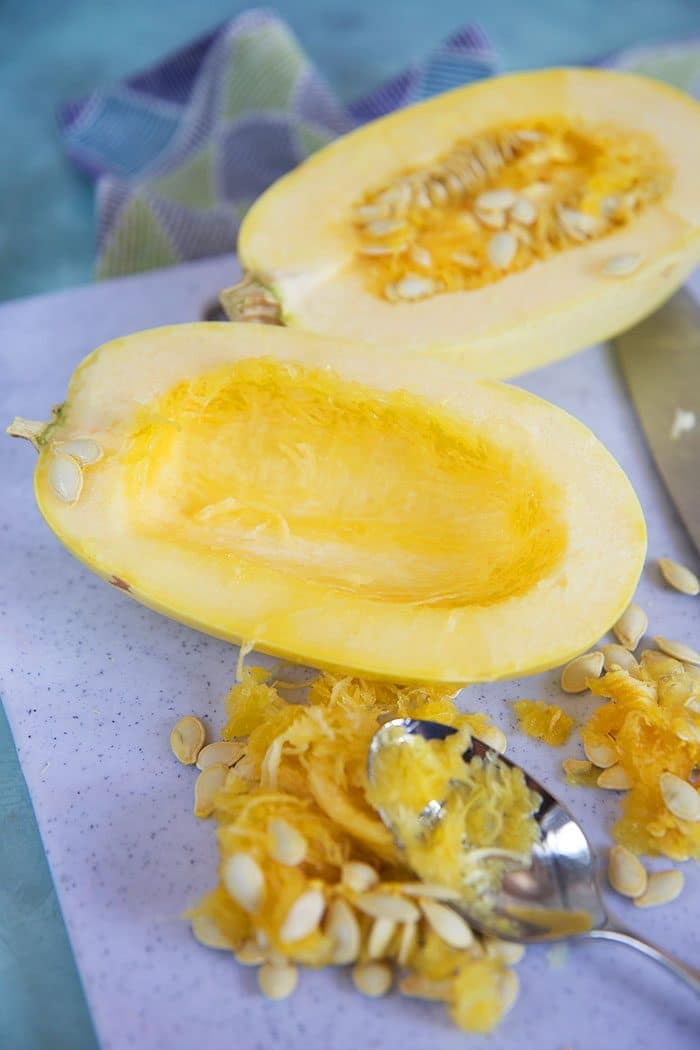 Spaghetti squash cut in half with seeds scooped out.