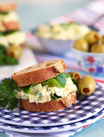 Bacon Horseradish egg salad on mini rye bread with lettuce on a blue and white plate.