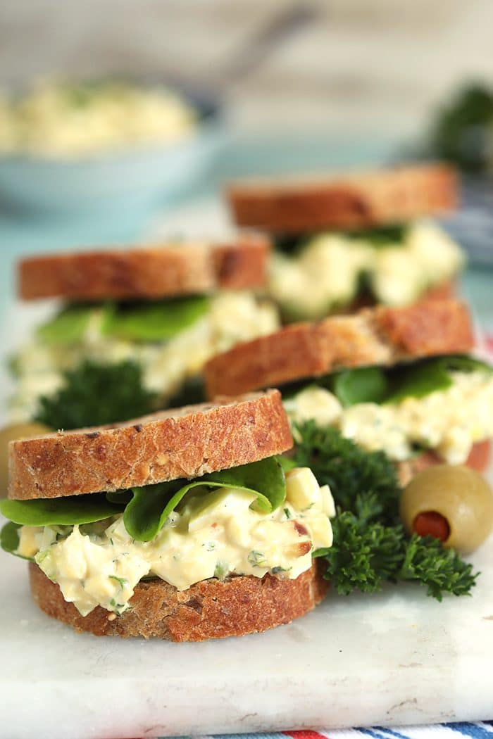 Egg salad sandwiches on a white marble board.