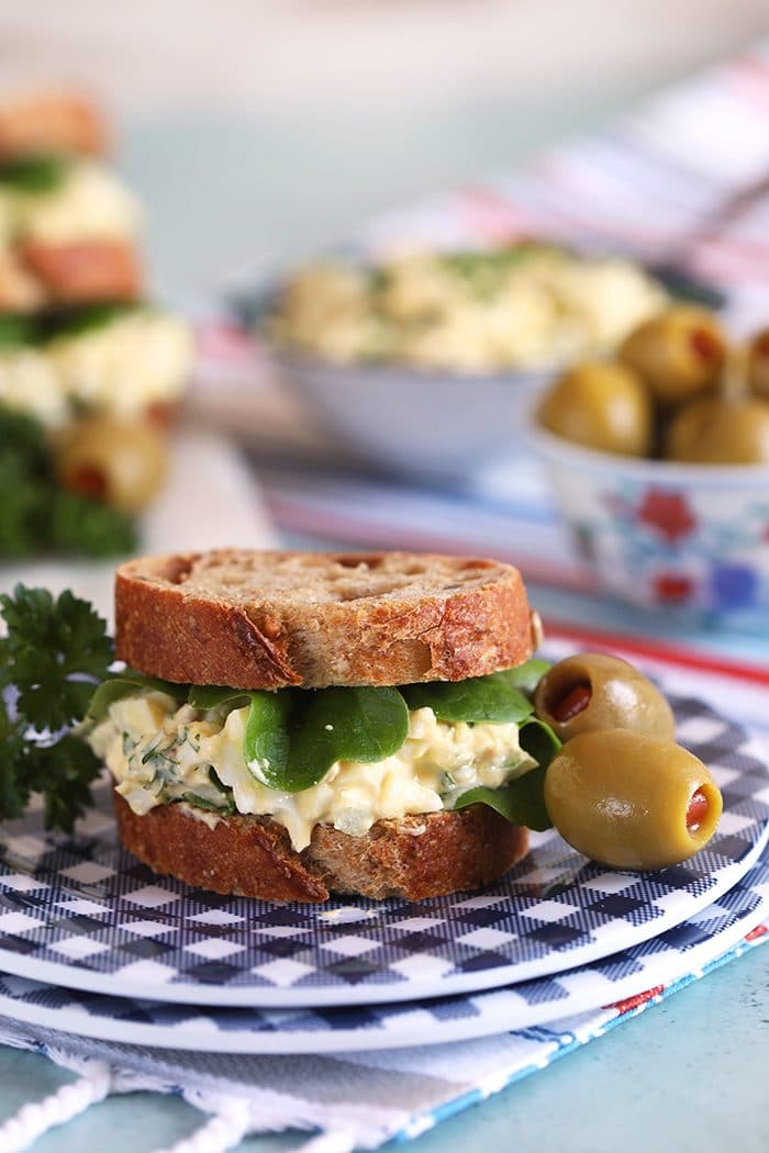 Egg salad sandwich with blue and white plates and an olive.
