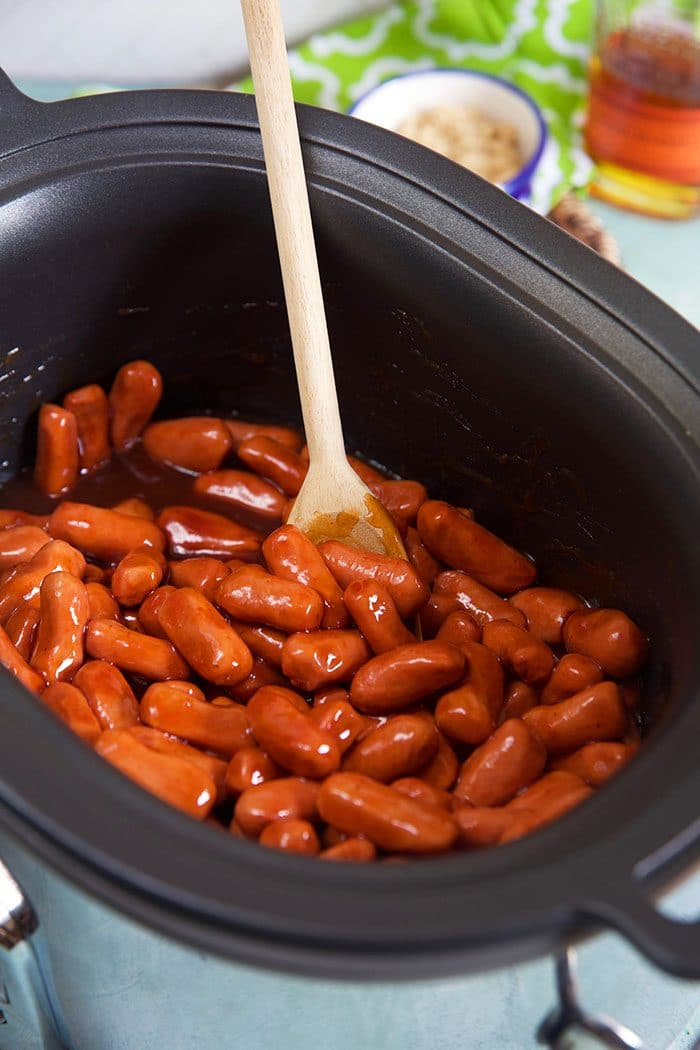 Little smokies in a slow cooker with a wooden spoon.