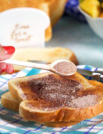 spoonful of cinnamon sugar sprinkled on a piece of cinnamon toast