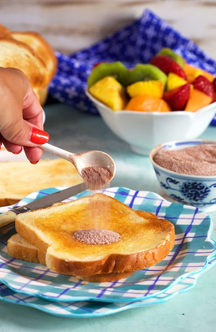 cinnamon sugar being sprinkled on a piece of cinnamon toast with a white spoon.