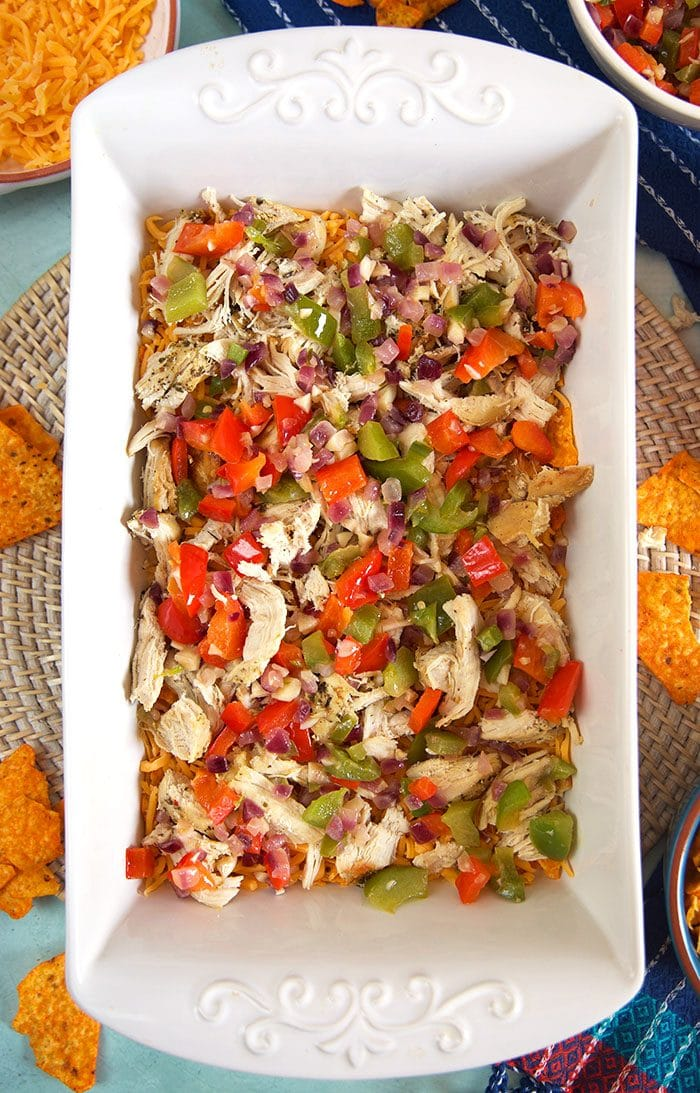 Layer of chicken and vegetables in a white casserole dish.