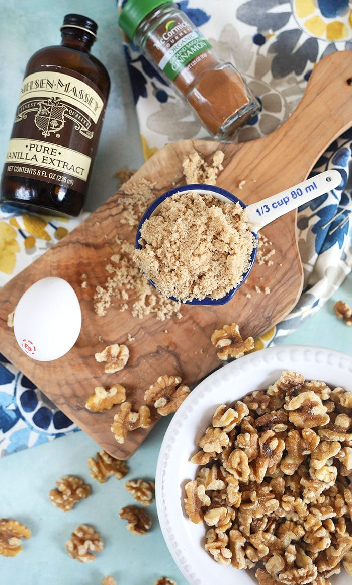 Ingredients for candied walnuts on a blue board.