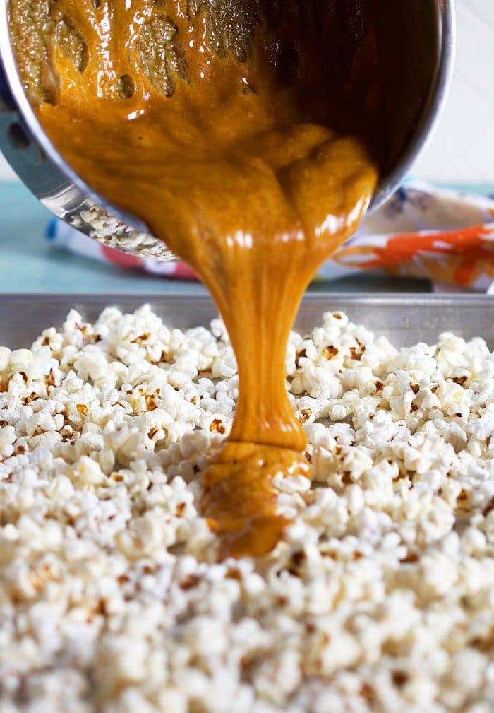 Caramel sauce being poured over popcorn on a baking sheet.