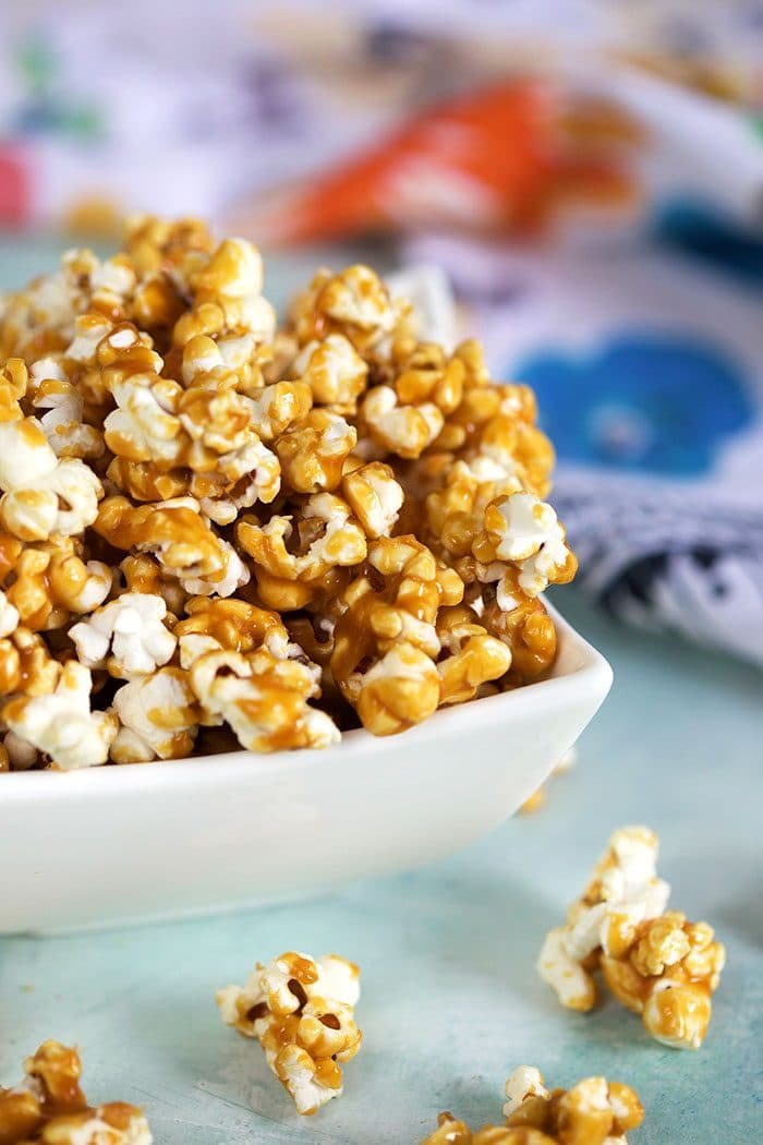Close up of caramel corn in a white bowl on a blue background.
