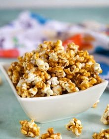 Caramel Popcorn in a white bowl on a blue background.