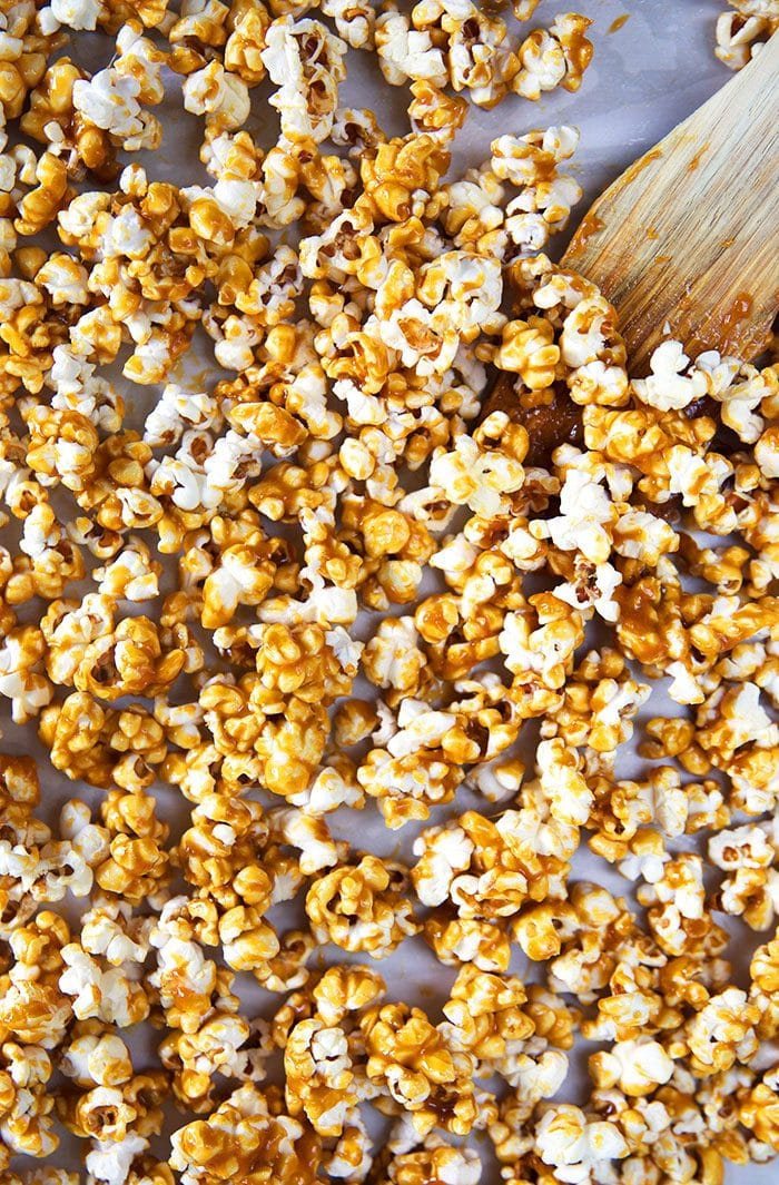 Overhead shot of caramel corn on a baking sheet with a wooden spoon.