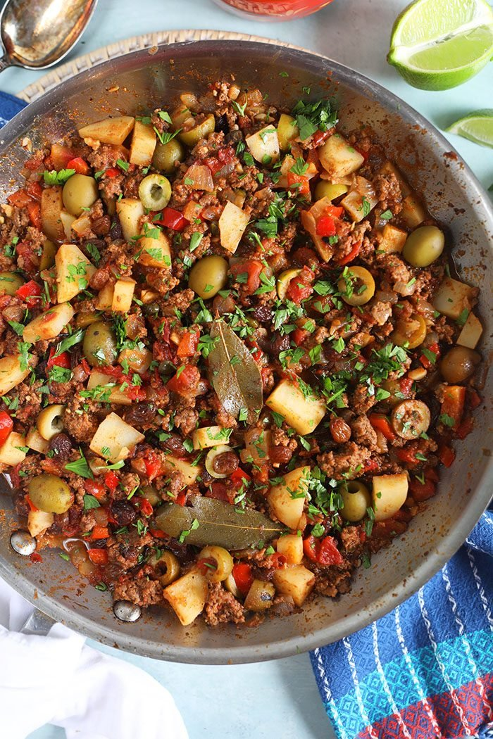Overhead shot of cuban Picadillo in a skillet with a lime.