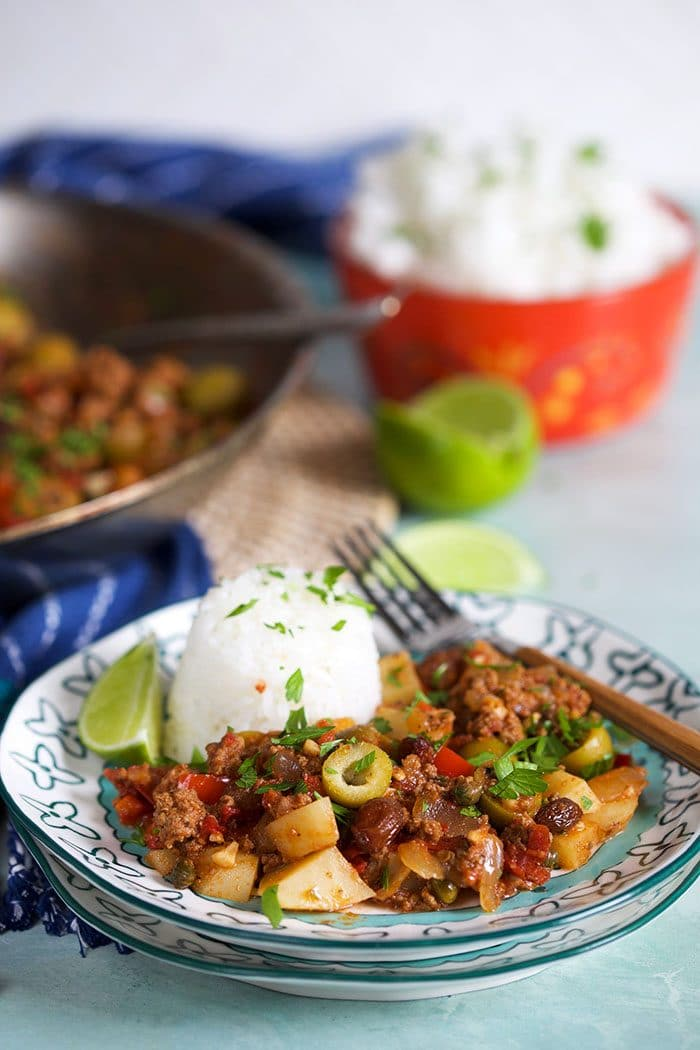Cuban Picadillo on a plate with a fork and rice.