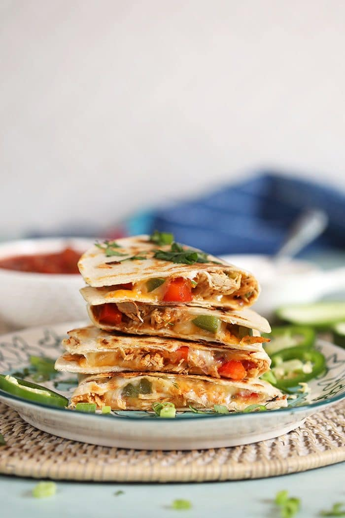 Stack of chicken quesadillas on a plate with cilantro.